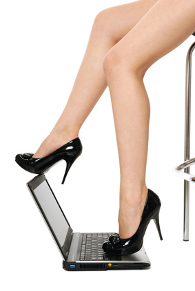 sexy legs over laptop isolated on white